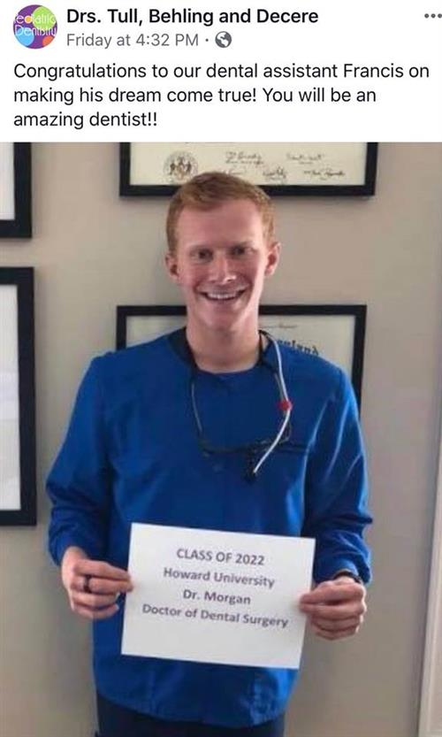 Picture of young man in blue scrubs holding a sign that reads: Class of 2022 Howard Univ. Dr. Morgan Dr. of Dental Surgery