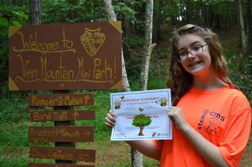STEM student girl holds a certificate of achievement next to her state park sign that she created in her back yard.