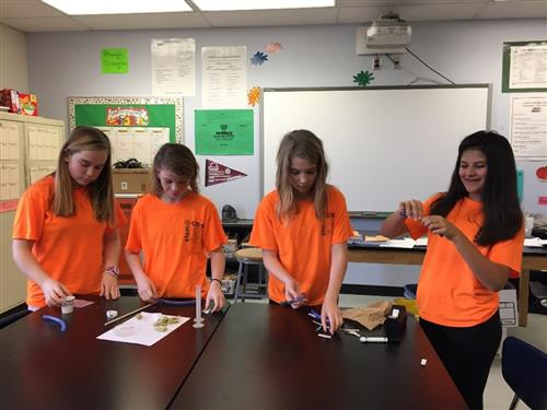 Four students in orange STEM shirts stand at a table with science materials preparing an experiment.