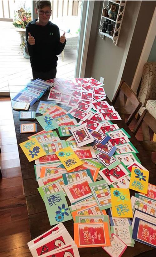 Student standing with two thumbs up in front of a table filled with colorful cards for healthcare workers and patients of COV