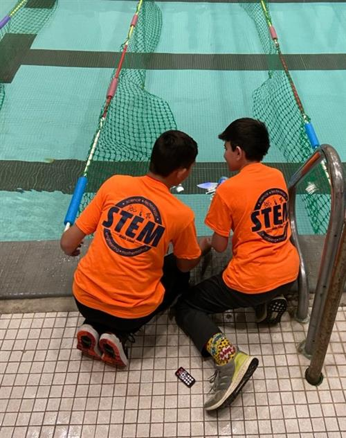The back of two boys in orange shirts sitting beside a pool with nets forming a path in the water.