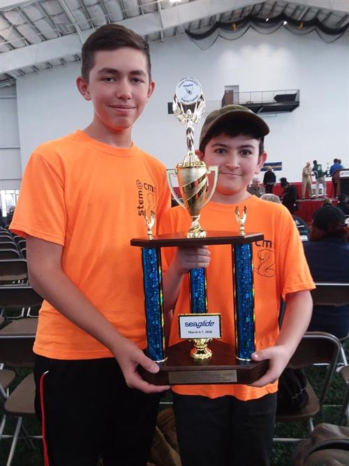 Two boys in orange shirts holding second place SeaGlide trophy.