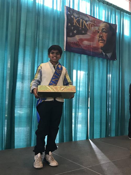STEM 6 student holds award on a stage with Martin Luther King Poster in the background for his winning video.
