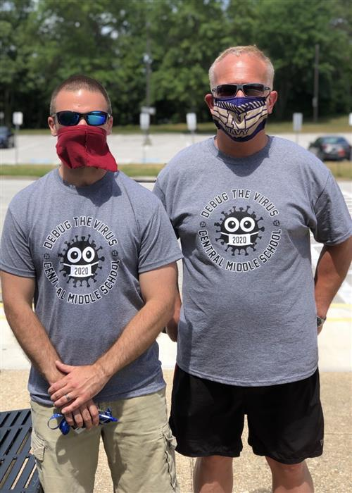 Two administrators wear masks and COVID 19 STEM Strong T-shirts prepared to help students pick up their school materials.