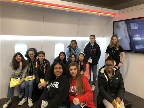 Twelve girls pose for a picture at Collins Aerospace to celebrate Girls in Engineering Day.