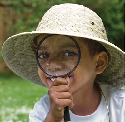 Girl wearing hat looking through magnifying glass