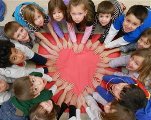 Group of childrening forming a heart with their hands.