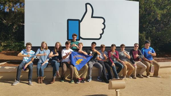 Students in front of Facebook thumbs up logo holding their Severna Park school banner and giving thumbs up.