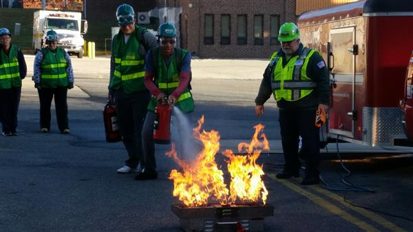 Students with protective gear practice putting out a fire with a fire extinguisher.