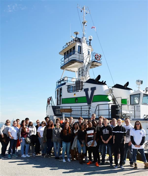 Group of Signature students in front of a ship during PortFest.