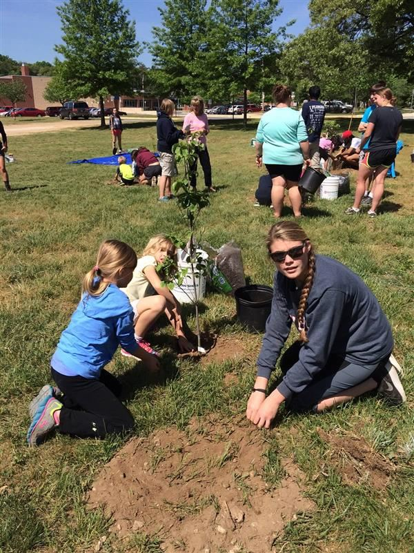 Signature high school students working with elementary students to plant trees.