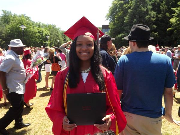 Female student in red cap and gown at graduation
