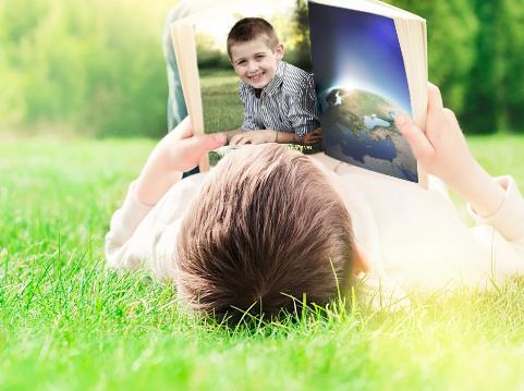 Boy lying in the grass reading with a book that shows the world and himself