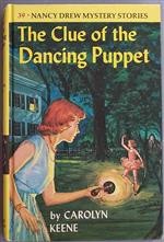 Nancy Drew, The Clue of the Dancing Puppet book cover;  Red-haired girl in a blue dress shines a flashlight at a puppet