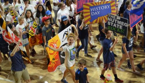 young people carrying colorful flags and posters promenading in a gym